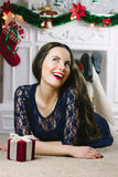 Christmas Woman. Beauty Model Girl with Fireplace on Background.  Gift in Hand. Open Mouth Beautiful Teeth Smile. True Stock Images