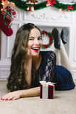 Christmas Woman. Beauty Model Girl with Fireplace on Background.  Gift in Hand. Open Mouth Beautiful Teeth Smile. True Stock Photos