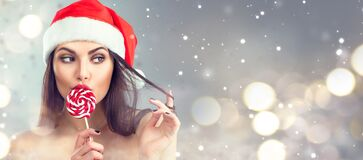 Free Christmas Woman. Beauty Model Girl In Santa Claus Hat With Red Lips And Xmas Lollipop Candy. Closeup Portrait Royalty Free Stock Photo - 202745455