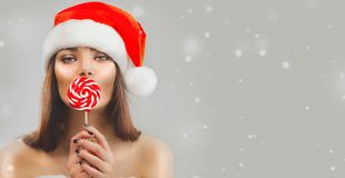 Free Christmas Woman. Beauty Model Girl In Santa Claus Hat With Red Xmas Lollipop Candy, Gift. Sales. Surprised Expression Stock Images - 162225544