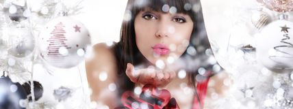 Christmas woman blowing glitter on christmas background Royalty Free Stock Images