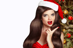 Christmas Woman. Brunette Girl in Santa Hat with red lips isolat Stock Image
