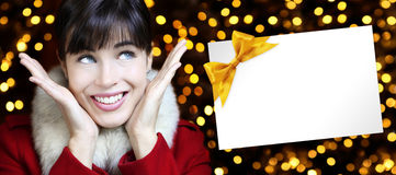 Christmas woman with card in golden lights background Stock Photography