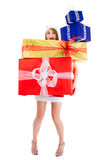 Christmas woman carrying gift pile. Overloaded christmas woman carrying gift pile on white Stock Image