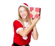 Christmas woman checking the gift box Royalty Free Stock Image