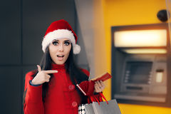 Christmas Woman Checking her Wallet in Front of a Bank ATM Stock Images