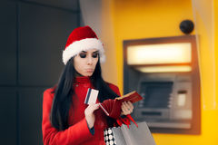 Christmas Woman Checking her Wallet in Front of a Bank ATM Stock Photo