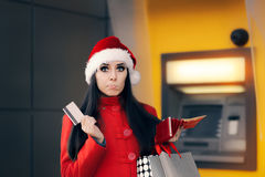 Christmas Woman Checking her Wallet in Front of a Bank ATM Royalty Free Stock Photo