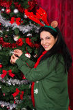 Christmas woman decorates tree Stock Images