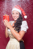 Christmas woman in dirndl with packet during snowfall Royalty Free Stock Photo
