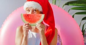 Christmas Woman eating watermelon in swimsuit. Christmas Woman eatig watermelon near the Pool. Funny girl celebrating Christmas in a resort Royalty Free Stock Photography