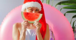 Christmas Woman eating watermelon in swimsuit. Christmas Woman eatig watermelon near the Pool. Funny girl celebrating Christmas in a resort Stock Photos