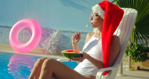 Christmas Woman eating watermelon at the Pool. Christmas Woman eatig watermelon at the Pool. Funny girl celebrating Christmas in a resort Royalty Free Stock Photos