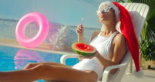 Christmas Woman eating watermelon at the Pool. Christmas Woman eatig watermelon at the Pool. Funny girl celebrating Christmas in a resort Stock Image