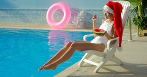 Christmas Woman eating watermelon at the Pool. Christmas Woman eatig watermelon at the Pool. Funny girl celebrating Christmas in a resort Stock Images