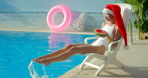 Christmas Woman eating watermelon at the Pool. Christmas Woman eatig watermelon at the Pool. Funny girl celebrating Christmas in a resort Royalty Free Stock Image