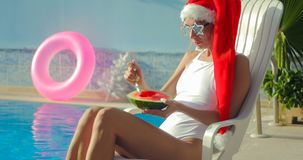 Christmas Woman eating watermelon at the Pool. Christmas Woman eatig watermelon at the Pool. Funny girl celebrating Christmas in a resort Stock Photos