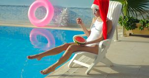 Christmas Woman eating watermelon at the Pool. Christmas Woman eatig watermelon at the Pool. Funny girl celebrating Christmas in a resort Royalty Free Stock Photography