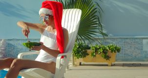Christmas Woman eating watermelon at the Pool. Christmas Woman eatig watermelon at the Pool. Funny girl celebrating Christmas in a resort Stock Photo