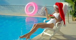 Christmas Woman eating watermelon at the Pool. Christmas Woman eatig watermelon at the Pool. Funny girl celebrating Christmas in a resort Royalty Free Stock Images