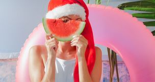 Christmas Woman eating watermelon in swimsuit. Christmas Woman eatig watermelon near the Pool. Funny girl celebrating Christmas in a resort Stock Photography