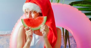 Christmas woman eating watermelon in swimsuit. Christmas woman eatig watermelon near the Pool. Funny girl celebrating Christmas in a resort Stock Photo