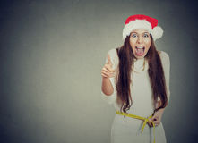 Christmas woman excited about weight loss measuring waist Royalty Free Stock Image