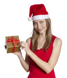 Christmas woman with gift. Beautiful young woman with Christmas hat unpacking gift box Royalty Free Stock Photo