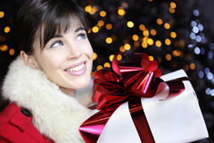 Christmas woman with gift package present, smiling and looks up Royalty Free Stock Photos