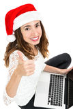 Christmas woman gives thumbs up. Christmas woman doing online shopping gives thumbs up. Isolated on white background Royalty Free Stock Photo