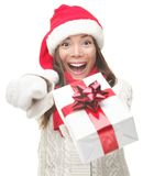Christmas woman giving gift excited. Christmas woman holding / giving gift excited pointing. Happy smiling woman in santa hat giving you a present being joyful Royalty Free Stock Photos