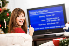 Christmas: Woman Happy About Winter Forecast. Pretty Asian-American woman doing Christmas related activities indoors - wrapping gifts, drinking cocoa, etc Royalty Free Stock Photos