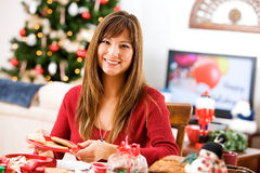 Christmas: Woman Having Fun Wrapping Baked Goods Royalty Free Stock Photography