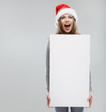 Christmas woman hold big white card. Santa hat. Isolated Stock Photos