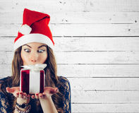 Christmas woman hold  gift in Santa hat isolated portrait . Smiling happy girl on white wood background. Royalty Free Stock Photography