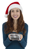 Christmas woman holding a gift box. Attractive woman with a santa claus hat holding silver colored gift box Royalty Free Stock Image
