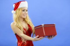 Christmas woman holding gift wearing Santa hat. Isolated on blue Royalty Free Stock Image