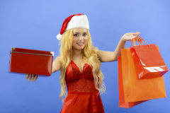 Christmas woman holding gift wearing Santa hat. Isolated on blue Royalty Free Stock Photo