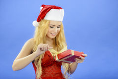 Christmas woman holding gift wearing Santa hat. Isolated on blue Royalty Free Stock Images