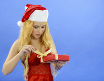 Christmas woman holding gift wearing Santa hat. Isolated on blue Stock Image