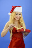 Christmas woman holding gift wearing Santa hat. Isolated on blue Stock Images