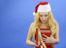 Christmas woman holding gift wearing Santa hat. Isolated on blue Royalty Free Stock Photography