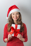 Christmas woman holding gifts. Christmas Santa hat  woman portrait hold christmas gift. Smiling happy girl Royalty Free Stock Image