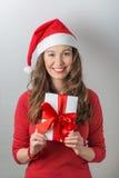 Christmas woman holding gifts. Christmas Santa hat woman portrait hold christmas gift. Smiling happy girl royalty free stock image