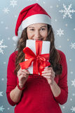 Christmas woman holding gifts. Christmas Santa hat  woman portrait hold christmas gift. Smiling happy girl Stock Photos