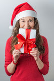 Christmas woman holding gifts. Christmas Santa hat  woman portrait hold christmas gift. Smiling happy girl royalty free stock photo