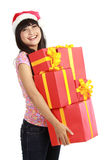 Christmas woman holding gifts wearing Santa hat Stock Image