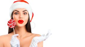 Christmas woman. Joyful model girl in Santa`s hat with lollipop candy pointing hand, proposing product. Surprised expression royalty free stock photos