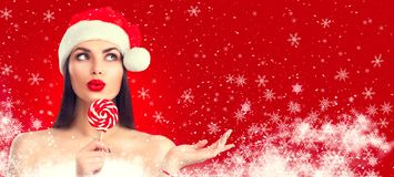 Christmas woman. Joyful model girl in Santa`s hat with lollipop candy pointing hand, proposing product. Surprised expression stock images