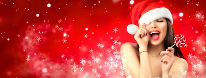 Christmas woman. Joyful model girl in Santa`s hat with red lips and lollipop candy in her hand. Closeup portrait over red background royalty free stock images
